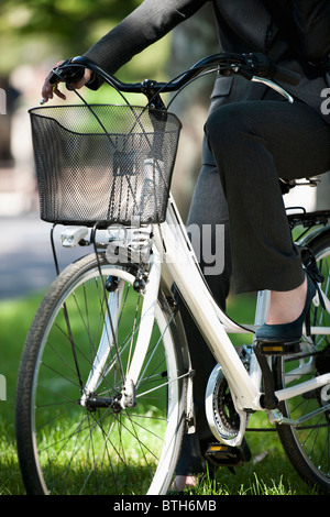 Woman in suit on bicycle - Stock Photo