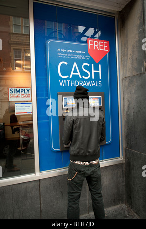 A man withdrawing cash from an Nationwide Building Society ATM - Stock Photo