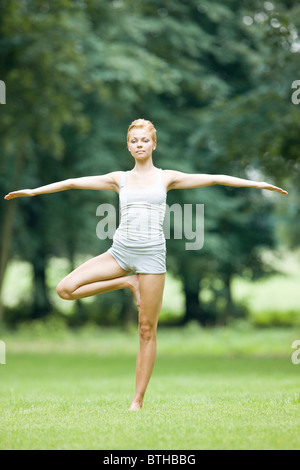 woman doing yoga in park - Stock Photo