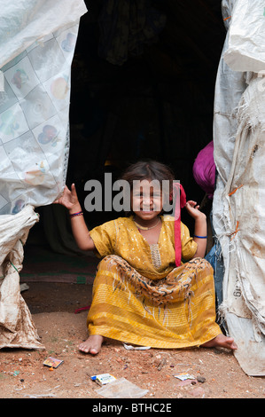 Poor indian lower caste baby girl in the doorway of her tent home made from plastic sacks. Andhra Pradesh, India - Stock Photo
