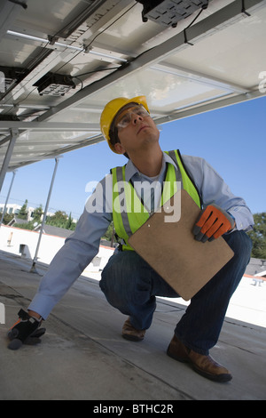 Maintenance worker checking solar panel in Los Angeles, California - Stock Photo