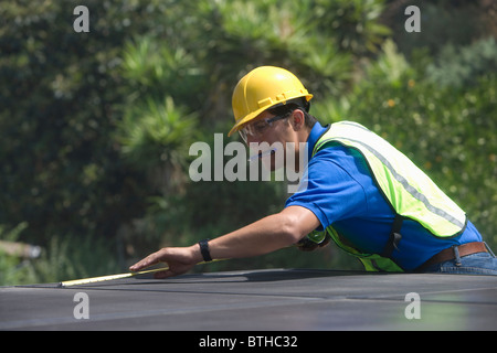 Maintenance worker measures solar array on rooftop, Los Angeles, California - Stock Photo
