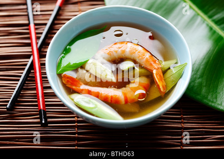 asian shrimp soup with kaffir leaves and spring onions - Stock Photo