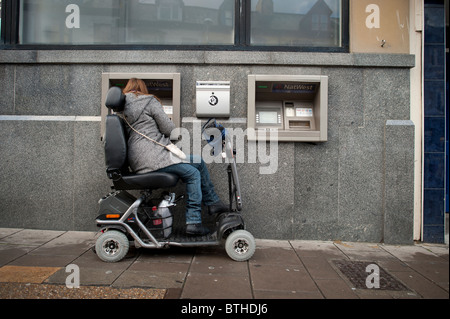 a woman in a powered wheelchair scooter using an ATM cash machine, UK - Stock Photo