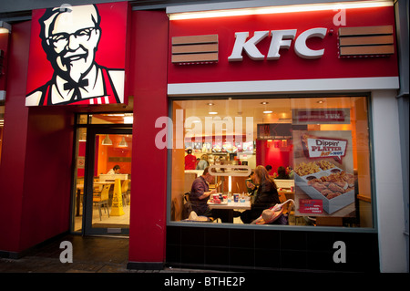 Exterior, night, people eating in a branch of KFC, kentucky fried chicken, fast food restaurant, UK - Stock Photo