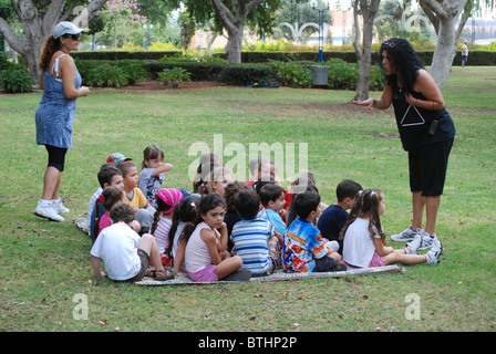 Israel, Preschool teacher with a group of preschool children in a park - Stock Photo