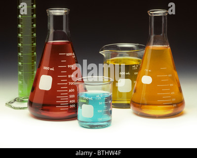 Scientific glassware filled with colored liquids on a graduated background - Stock Photo