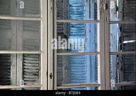 Broken glass and wooden peeling window shutters background in derelict house. - Stock Photo
