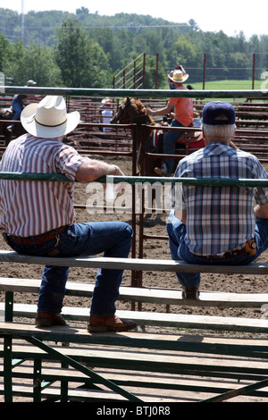 Two older cowboys sitting in the stands watching rodeo competitions in Wisconsin - Stock Photo