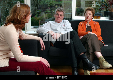 Teenage girl talking with annoyed parents on sofa at home. - Stock Photo