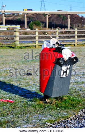 overflowing dog bin filled with plastic bags of rubbish and litter - Stock Photo