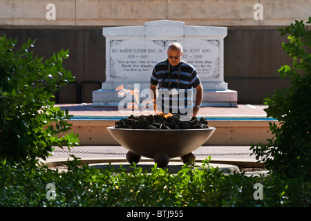 African American visitor in front of Eternal Flame with MLK tomb behind, Martin Luther King Historic Site, Atlanta, - Stock Photo