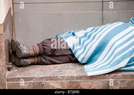 A homeless person sleeping rough in a doorway in london, UK. - Stock Photo