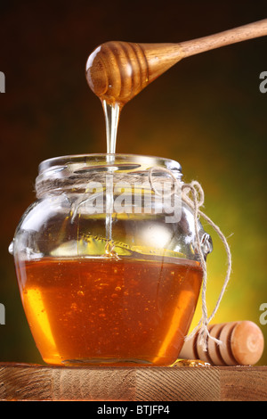 Sweet honey pouring from drizzler into the pot. Pot is on wooden table. - Stock Photo