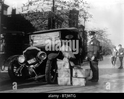 Prohibition, a policeman standing alongside a wrecked car and cases of moonshine, November 16, 1922. - Stock Photo