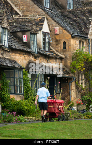A postman delivering the mail in the rural Cotswalds, England - Stock Photo