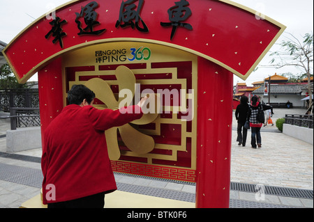 A Chinese woman spins a wheel on ngong ping 360 red and gold welcome sign outside Ngong Ping Village on Lantau Island, - Stock Photo