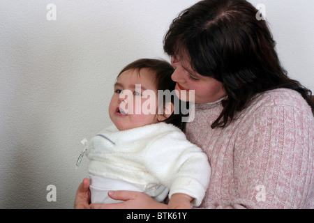 Mother comforting and holding her plus sized upset baby girl having a temper tantrum. - Stock Photo