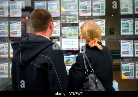 Young couple looking at houses in estate agents window - Stock Photo