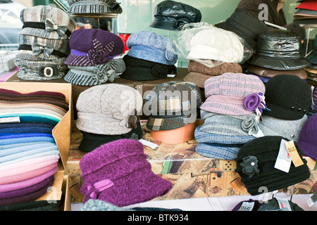 Various sizes and coloured ladies hats on a market stall - Stock Photo