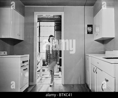Women enters a modern 1940s kitchen with white enameled metal cabinets.  The housing was built by the government - Stock Photo