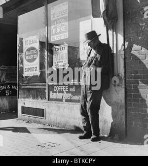 Lone man in farmer's overalls, on San Francisco's Skid Row at Howard Street. Ruined farmers from the Midwest added - Stock Photo
