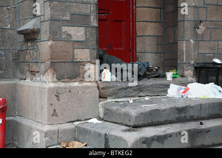 A homeless man lying on a staircase, New York City, USA - Stock Photo