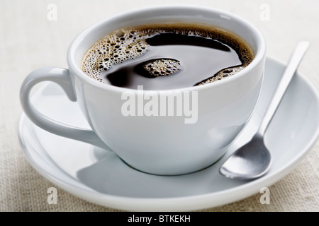 cup of freshly brewed black coffee, focus is on the middle bubbles - Stock Photo
