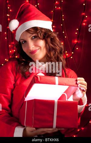 Smiling Santa Woman Opening a Present - Stock Photo