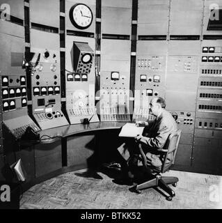 Enrico Fermi (1901-1954), seated at control panel of a particle accelerator, in 1951. He won the 1938 Nobel Prize - Stock Photo