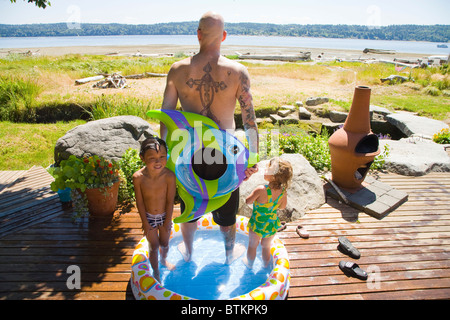 man with kids in wading pool near beach - Stock Photo