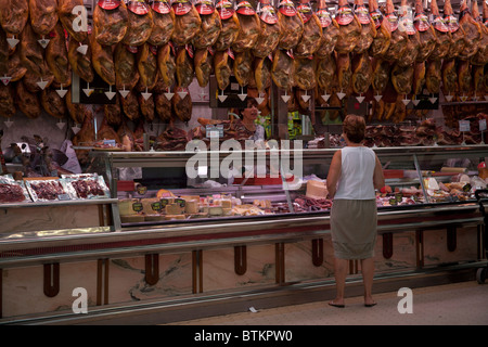 Woman buying meat from a stall in the Mercado Central, Valencia Spain - Stock Photo