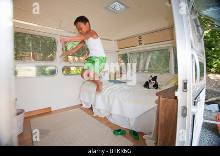 boy and dog on bed in camper - Stock Photo