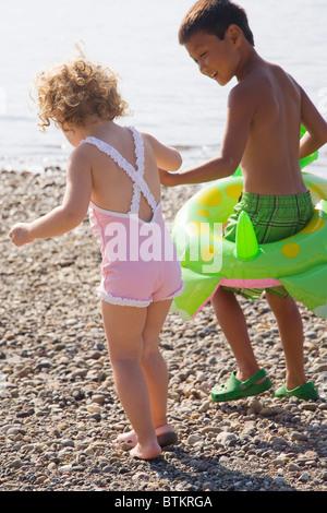 boy helping girl walk on rocky beach - Stock Photo