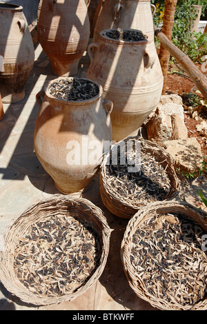 Salted and dried olives stored in jars and baskets at an olive farm. Crete, Greece. - Stock Photo