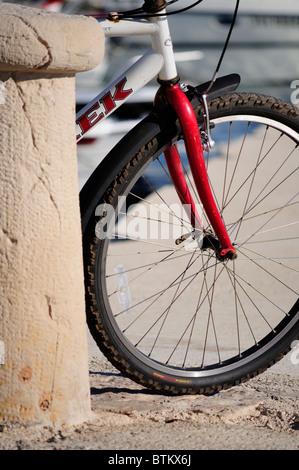 Detail of bicycle leaning on stone bollard, Silba Island, Croatia - Stock Photo