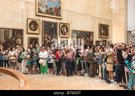 Visitors in front of Mona Lisa Louvre Museum Paris - Stock Photo
