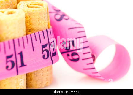 Unhealthy eating concept: Cakes rounded inch scale measuring tape. Shallow depth of field - Stock Photo