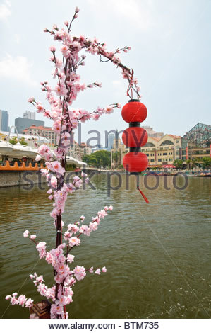 Red lanterns and artificial flowers found on a boat trip along the Singapore River at the popular and trendy Clarke - Stock Photo