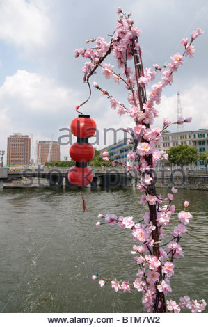 Red lanterns and artificial flowers found on a boat trip along the Singapore River, Singapore, Southeast Asia, Asia - Stock Photo