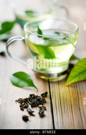 closeup of dry green tea, and a cup with fresh green tea. in the background, out of focus cup with fresh tea - Stock Photo