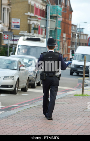 British policeman on the beat in London, rear view - Stock Photo
