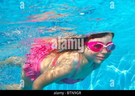 underwater little girl pink bikini goggles blue swimming pool - Stock Photo