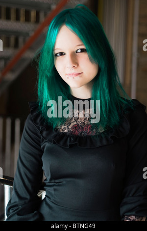 A young goth woman with green hair wearing a green dress and standing in a fire escape. - Stock Photo