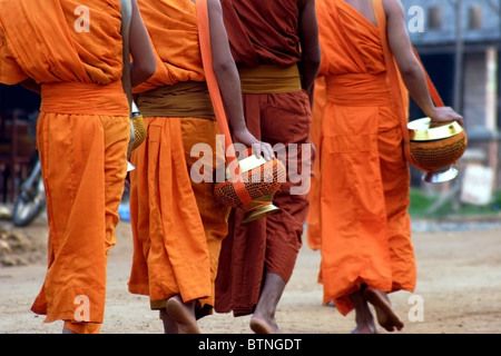A group of Buddhist monks are walking on a dirt street with bare feet holding their bowls in Vang Vieng, Laos. - Stock Photo