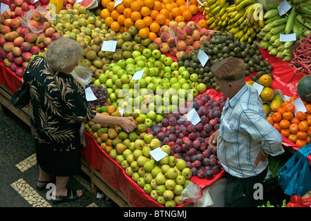 Mercado dos Lavradores fruit seller and customer fruit and vegetable market Funchal Madeira Portugal - Stock Photo