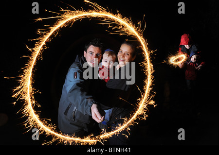 Young couple and child with sparkler on bonfire night - Stock Photo