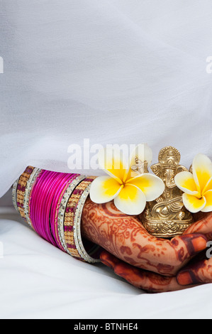 Indian girl wearing white silk sari with henna hands holding a Frangipani flower and a statue of Ganesha. India - Stock Photo