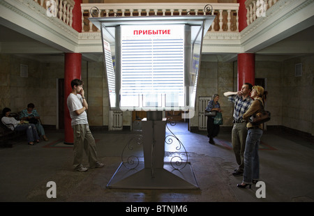 Travellers in front of the arrival/departure board at a train station, Brest, Belarus - Stock Photo
