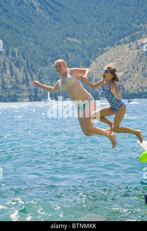 Sisters jumping off dock into lake - Stock Photo